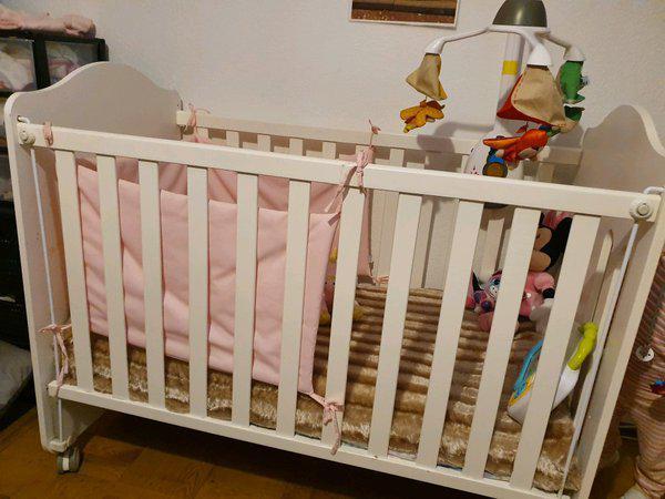 Cama e móvel com banheira de bebé.